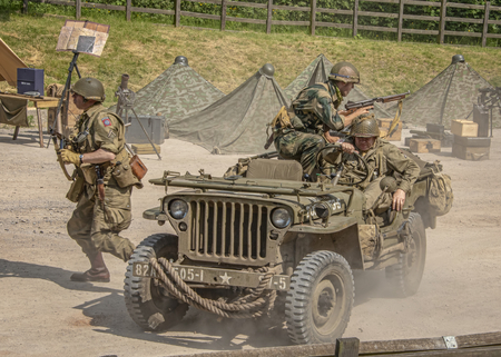 LEICESTERSHIRE,UK  - JUNE 03 2018: Men dressed in wartime US army soldiers uniform reenacting military maneuvers during Victory Day Europe Celebration Event at Great Central Railway, Quorn Editorial
