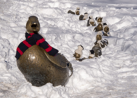 USA, Boston - January 2018: 'Make way for Ducklings' with Mrs Duck wearing her winter scarf, her babies in little woolen hats. Nancy Schön's magical sculpture.