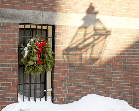 USA, Boston - January 2018 - House with christmas wreath on railings in Beacon Hill Area - lamp reflcted in shaddow on wall 免版税图像 - 112894412