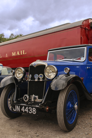 LEICESTERSHIRE,UK - MAY 2015: Riley sprots car exhibiing at a classic car show sits in fornt of a vintage royal mail train carriage