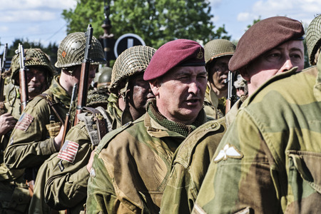 LEICESTERSHIRE,UK  - JUNE 07 2015: Men dressed in wartime US army soliders uniform reenacting military manouvers during Victory Day Europe Celebration Event at Great Central Railway, Quorn Editorial