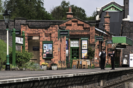 ROTHLEY Great Central  Steam railway, UK - 2015 :  A Station Master and his colleague stand and talk on the platform outside a closed cafe in a vintage train station Editorial