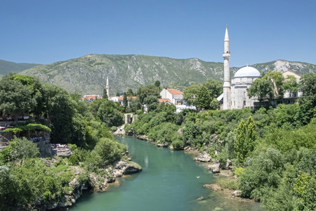 BIH, Mostar - June 2018: The Koski Mehmed Pasha Mosque as seen from the old bridge. Substantially rebuilt after the war, this 1618 domed mosque has a  minaret that gives views over the town