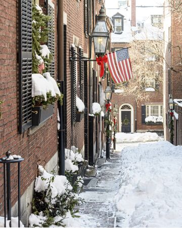 USA, Boston - January 2018 - Acorn Street in the snow with the American flag flying 免版税图像