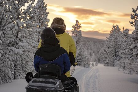 Finland, Inari - January 2019: 2 people riding on a snowmobile through the wilds of Lapland, under a red sky Standard-Bild