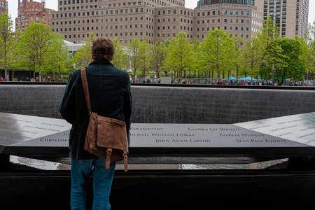 USA, New York - May 2019: Man pauses at 9/11 monument, World Trade Centre