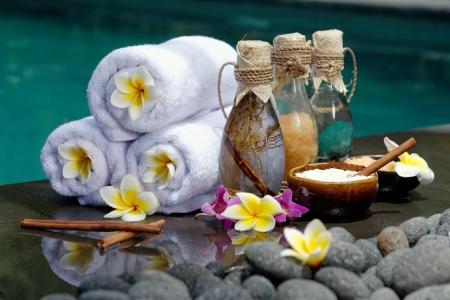 Im Spa-Konzept in einer Luxus-Villa auf der Insel Bali mit, Massage-Öl, Bad-Salz, Vulkansteine, Körperpeeling, Handtücher, Zimtstangen, Orchideen und Blumen Lizenzfreie Bilder