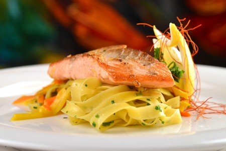 Grilled salmon steak on ribbon pasta  photo