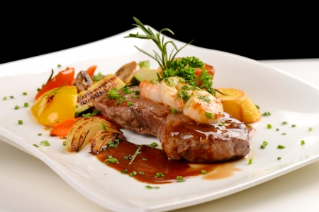 Delicious juicy barbequed steak and prawns with grilled tomato and roasted potatoes  Surf and Turf style  Shallow dof