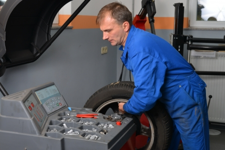 wheel balancing: Wheel Balancing, Auto mechanic spins a car wheel as he waits for the machine to tell him he s reached the right spot to add a balancing weight