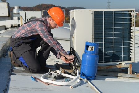 building maintenance: Air Conditioning RepairYoung repairman on the roof fixing air conditioning systemModel is actual electrician  Stock Photo
