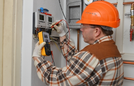 building maintenance: Electrician at work with his instrument of measurement  Stock Photo