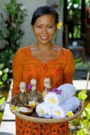 Massage therapist at the luxury Spa on Bali Island holding tray with  Massage oil, bath salt, body scrub, Towels,Cinnamon sticks, Orchids and frangipani flowers  photo