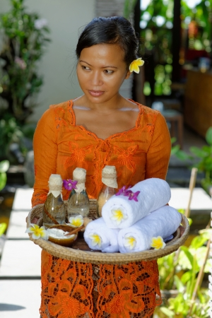 bali massage: Massage therapist at the luxury Spa on Bali Island holding tray with  Massage oil, bath salt, body scrub, Towels,Cinnamon sticks, Orchids and frangipani flowers  Stock Photo