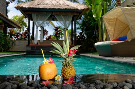 Tropical cocktails by the pool, Nicely decorated coconut and pineapple cocktails on pool side in luxury villa on Bali island  photo