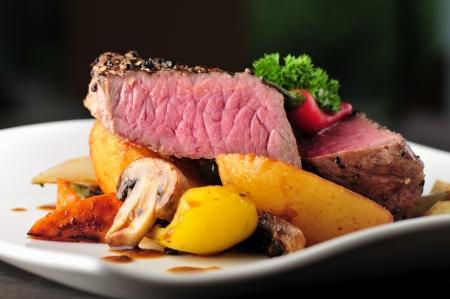 Jugoso filete con patatas al horno y champiñones, costilla de res seca envejecido primer grado eye steak cocinado papas fritas medianas raras Steak corte, pimienta, champiñones y el perejil en un plato