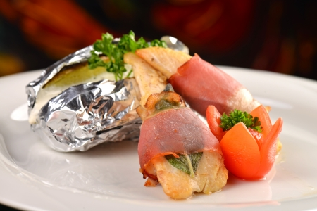 Saltimbocca - Italian speciality, veal chops with prosciutto and sage leaf, served with baked potato in alu foil  photo