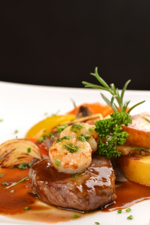 Köstliche saftig gegrilltes Steak und Garnelen mit gegrillten Tomaten und gerösteten Kartoffeln Surf and Turf Stil Shallow dof