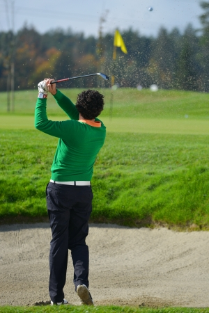 Golfer Sand trap, Golfer chipping the ball from sand trap  photo