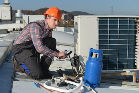 Klimaanlage Reparatur, junge Werker auf dem Dach Befestigungsklimaanlage Modell ist Elektriker tatsächlichen