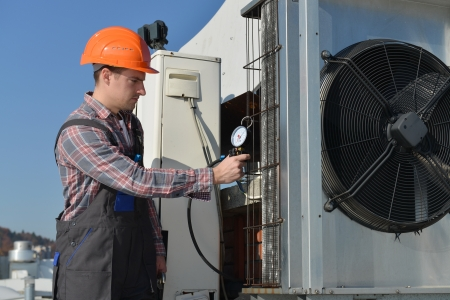 building maintenance: Air Conditioning Repair, young repairman on the roof fixing air conditioning system  Model is actual electrician   Stock Photo