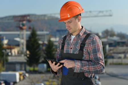 Engineer at construction site, an image from the construction industry of a worker with a computer tablet   photo