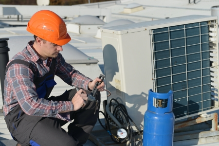 Air Conditioning Repair, young repairman on the roof fixing air conditioning system  Model is actual electrician   Stock Photo