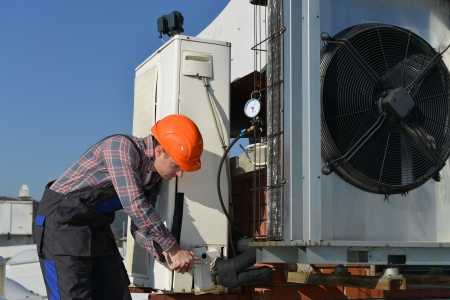 Air Conditioning Repair, young repairman on the roof fixing air conditioning system  Model is actual electrician   Imagens
