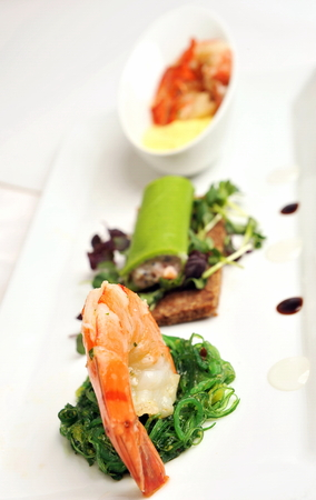 entree: Gourmet appetizer, starter or Entree of a french dish with seafood mixed among salad leaves
