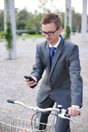 Portrait of young businessman on a bike using mobile phone, outdoors   photo