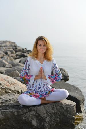 buena postura: Yoga por el oc�ano, mujer joven que hace yoga en la playa Foto de archivo