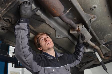 Car mechanic repairs exhaust system
