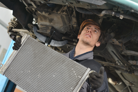 Car mechanic is Changing radiator  photo