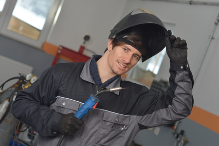Smiling welder in gray workwear and helmet at work place  photo