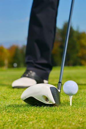Driver with golf ball on a tee and grass  photo