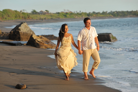 Beautiful beach marriage  the bride and groom against the blue ocean, shot on Bali island Indonesia  photo