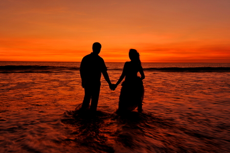 Silhouette   Shape of a bride and groom on the beach at sunrise time  photo