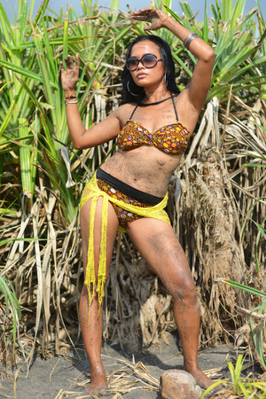 Beautiful Asian brunette model standing in front of scenic jungle  photo