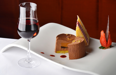 Chocolate and berries cake with glass of dessert wine  Imagens
