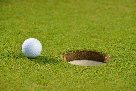 follow through: Golf ball on lip of cup