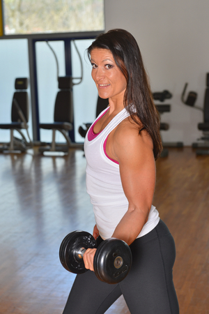 Smiling fitness woman lifting weights  photo
