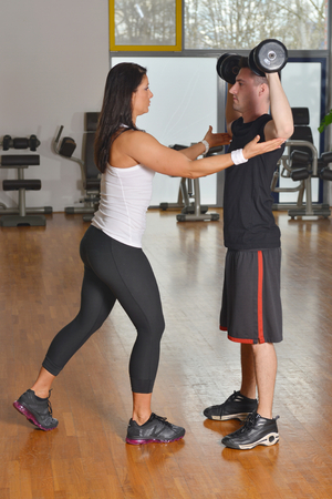 Female trainer working with her trainee with weight training equipment  photo