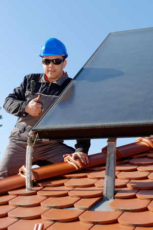 class maintenance: Man installing alternative energy photovoltaic solar panels on roof  Thumbs up