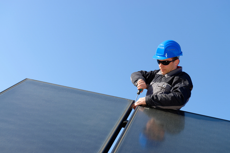 class maintenance: Man installing alternative energy photovoltaic solar panels on roof  Stock Photo
