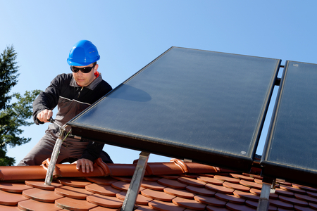 solar wind: Man installing alternative energy photovoltaic solar panels on roof  Stock Photo