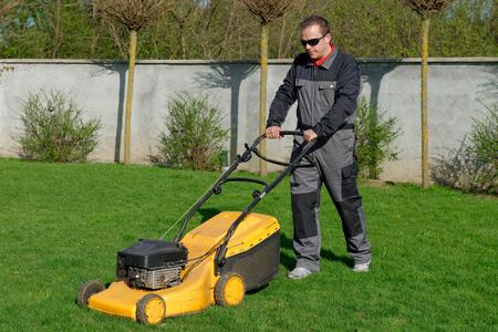 lawn mower: lawn mower man working on the backyard