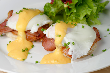 eggs and bacon: Eggs Benedict- toasted English muffins, ham, poached eggs, and delicious buttery hollandaise sauce