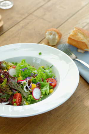 Fresh salad with tomatoes,cucumbers and bread baguete  green