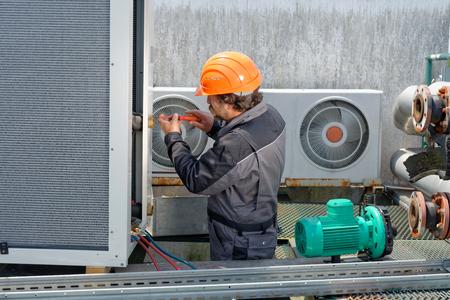 Klimaanlage Reparatur, Handwerker auf dem Dach Befestigungs riesige Klimaanlage