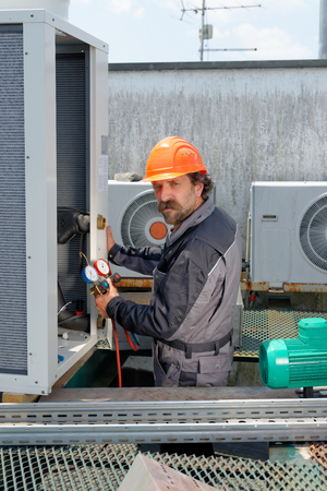 building maintenance: Air Conditioning Repair, repairman on the roof fixing huge air conditioning system
